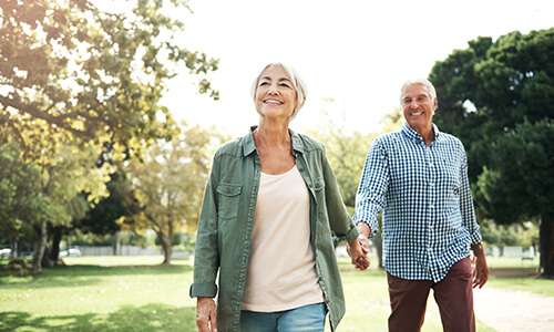 Older couple walking in the park holding hands and smiling because of the attention and guidance of their dentist in Seattle