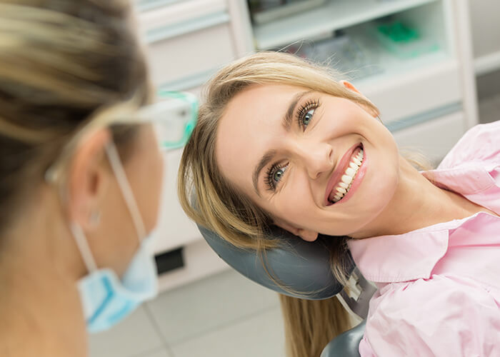 A patient smiling in the dental chair and looking up at her dentist in Seattle