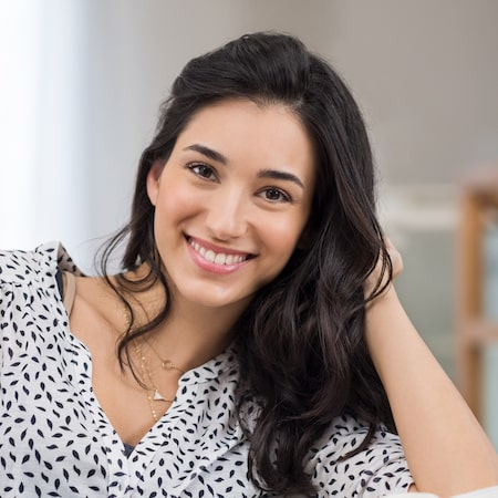 Dark-haired woman leaning on her arm and smiling