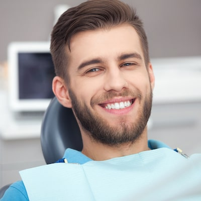 Young man with a beard smiling and wearing a dental bib