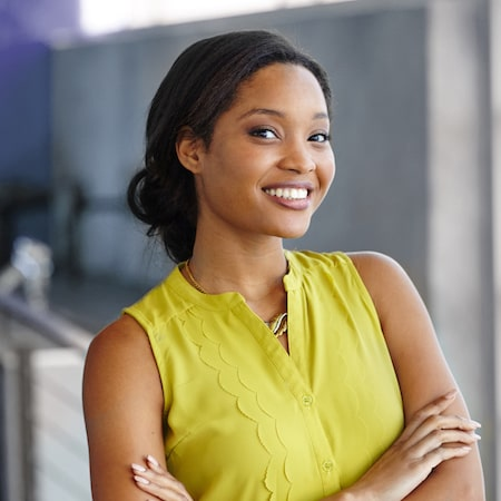 Professional woman standing with her arms folded and smiling