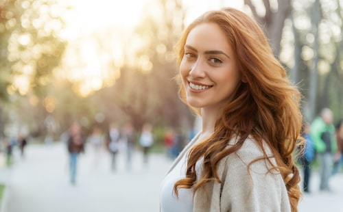 Beautiful woman looking over her shoulder while walking in an urban setting