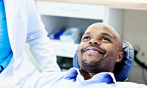 Image of a male patient smiling on dentist chair