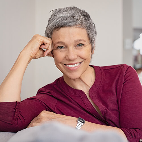 Image of a woman with short hair smiling on sofa