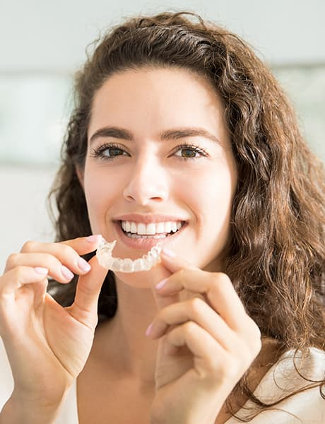 Woman putting on Invisalign aligners in Seattle, WA