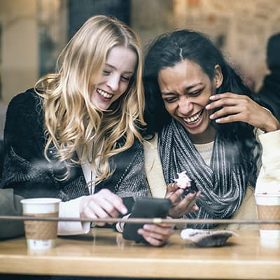 Women laughing in a Seattle coffee shop to show that with Invisalign in Seattle you can still eat and rink your favorite foods