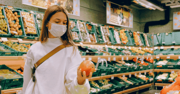 A woman wearing a mask in a grocery store holding a produce item follinw go