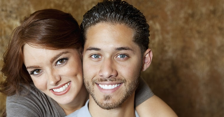 Man and woman smiling after a dental crown procedure at Love Your Smile