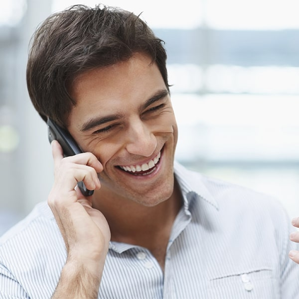 A man speaking on phone and smiling with new porcelain veneers from Love Your Smile