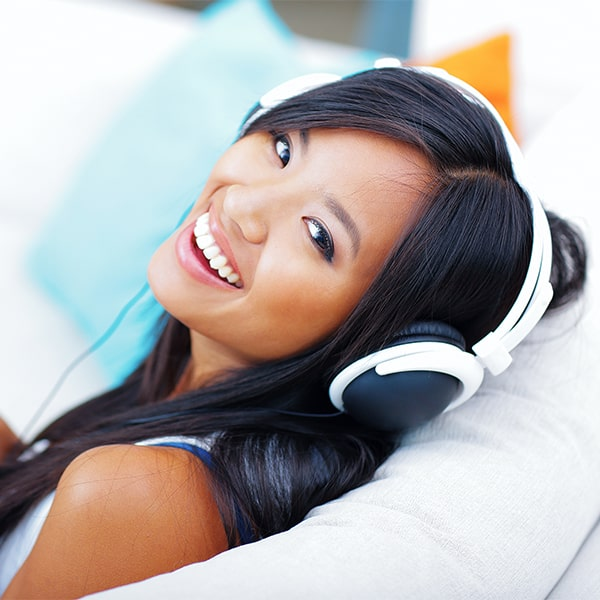 A woman listening to music with headphones after teeth whitening session at Love Your Smile
