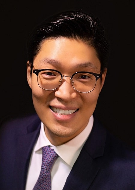 Dr. Lee smiling in a suit