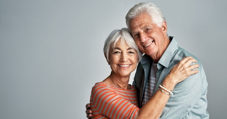 An older couple smiling showing off their dental implants