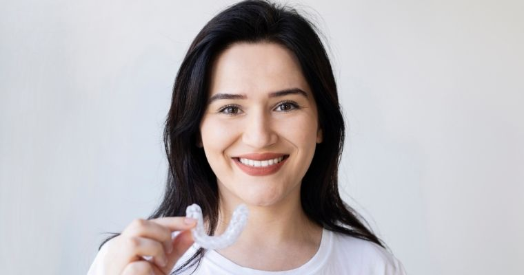 Woman smiling and holding up her clear aligner